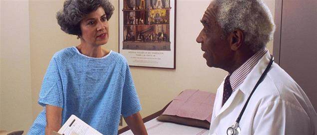 Doctor consults with a patient dressed in a medical gown in an examining room.