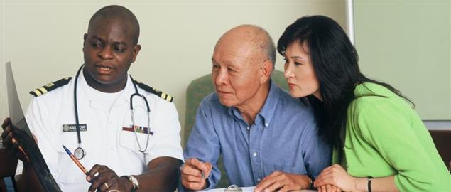 A military doctor explains X-Ray results to an elderly man and his daughter