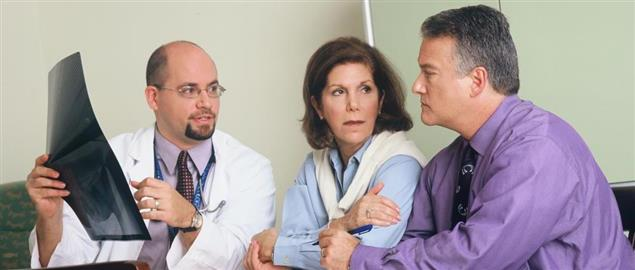 Doctor discussing X-ray results with a couple
